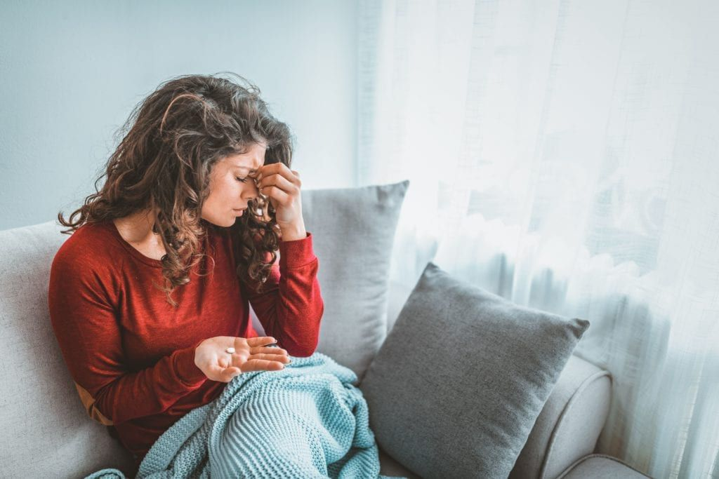 woman with headache and medication in her hand