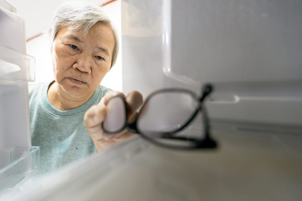 senior woman confused putting her glasses in the fridge