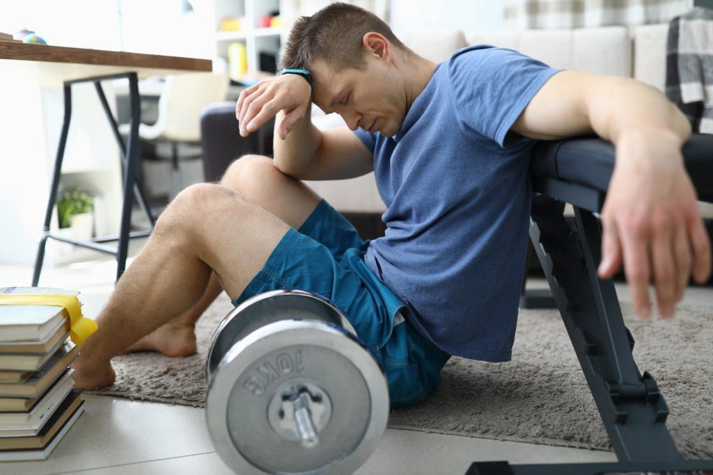 man holding his head after lifting weights