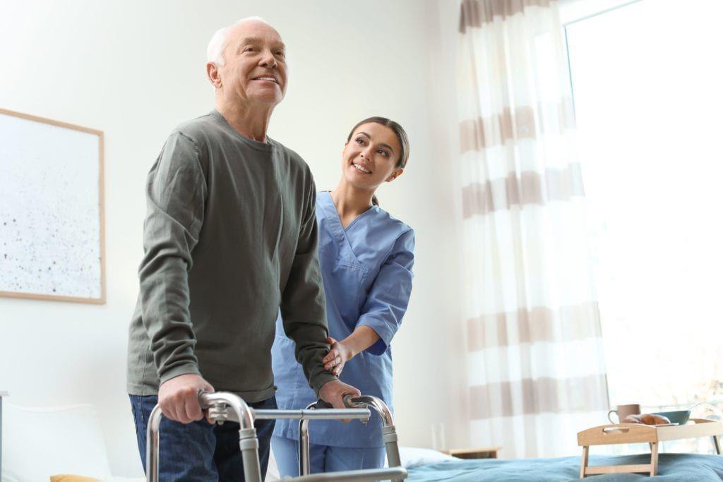 nurse helping older man with walker