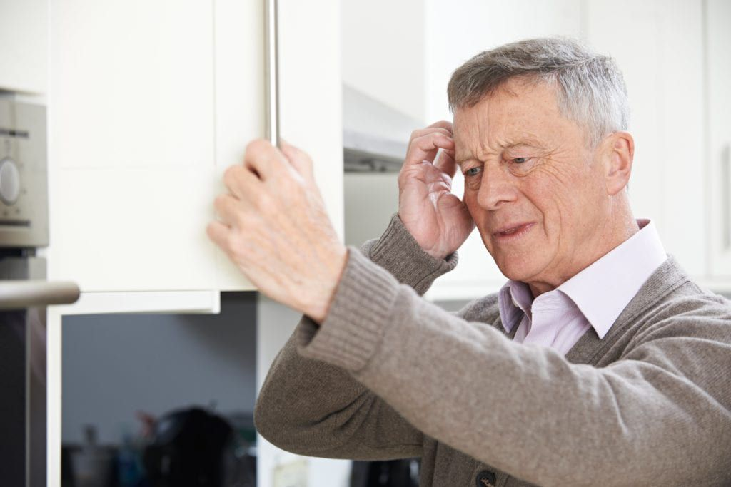 older man opening cabinet and looking confused