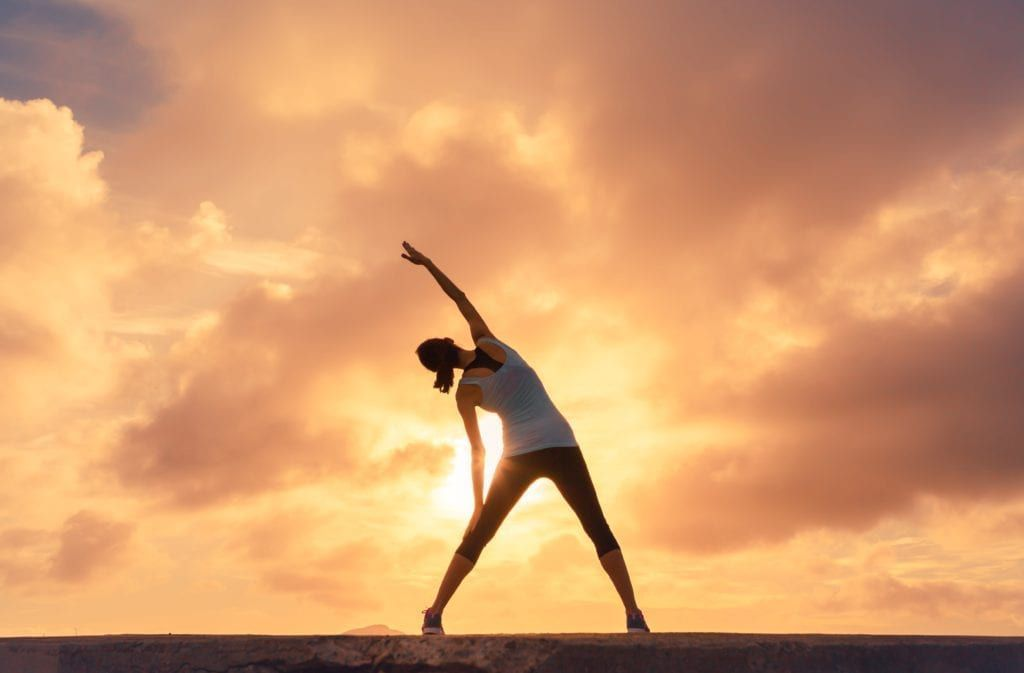 woman doing yoga against the sunset