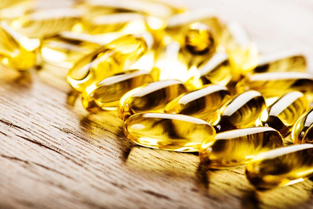fish oil capsules on a wood background